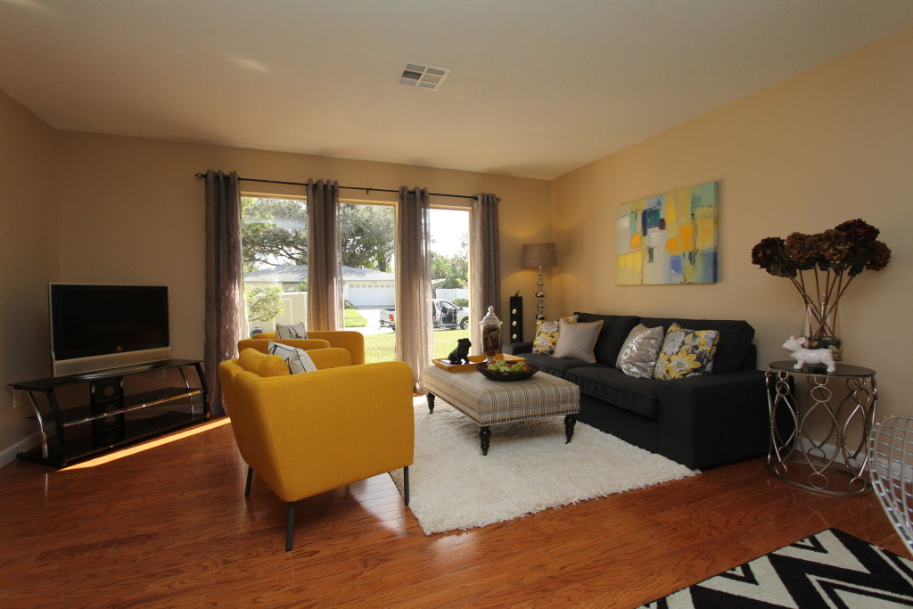 After the staging: This beautiful living room features three large architectural windows in beautiful nice updated style.